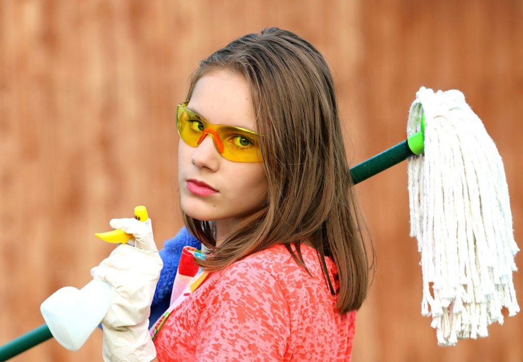 Coole Frau mit gelber Brille und Putzmittel in den Händen