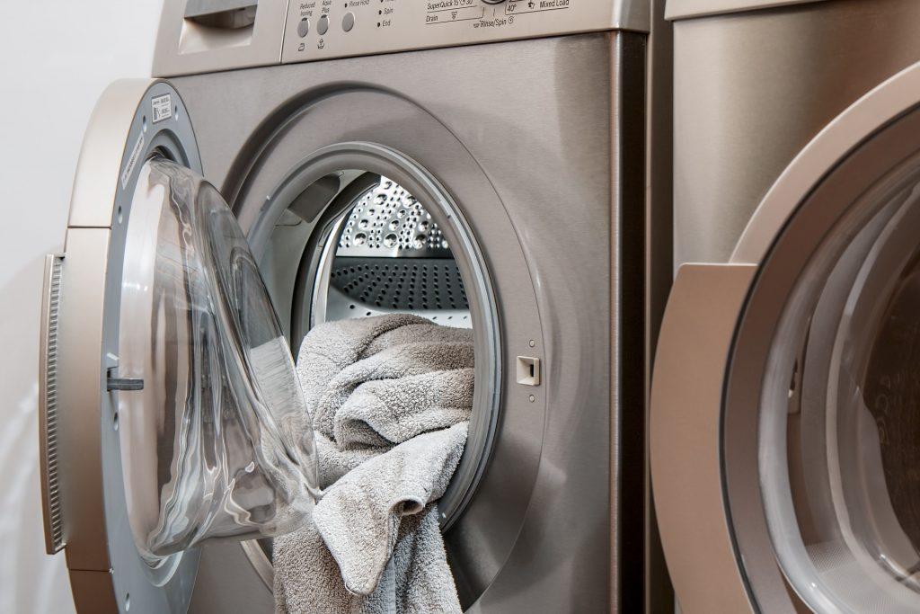 Zwei Waschmaschinen eine ist geöffnet und es ragen Handtücher heraus.